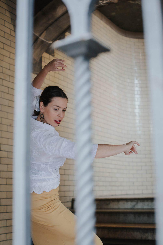 Flamenco dancer behind some iron bars in an urban setting