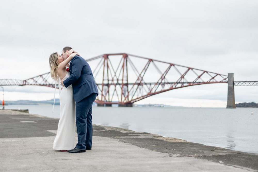 Wedding couple kissing in front of the forth rail bridge