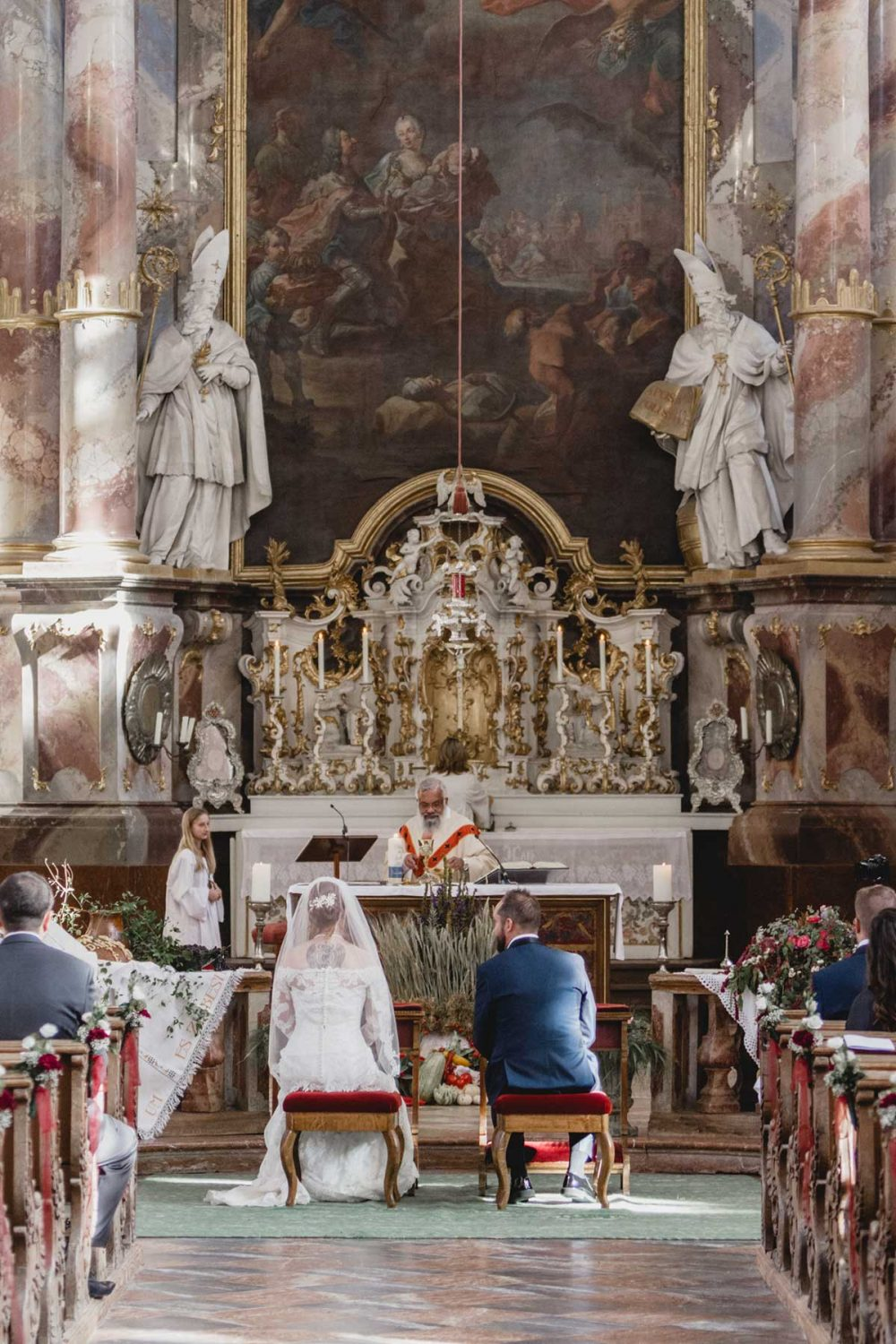 wedding couple sitting in front of the altar in a catholic church