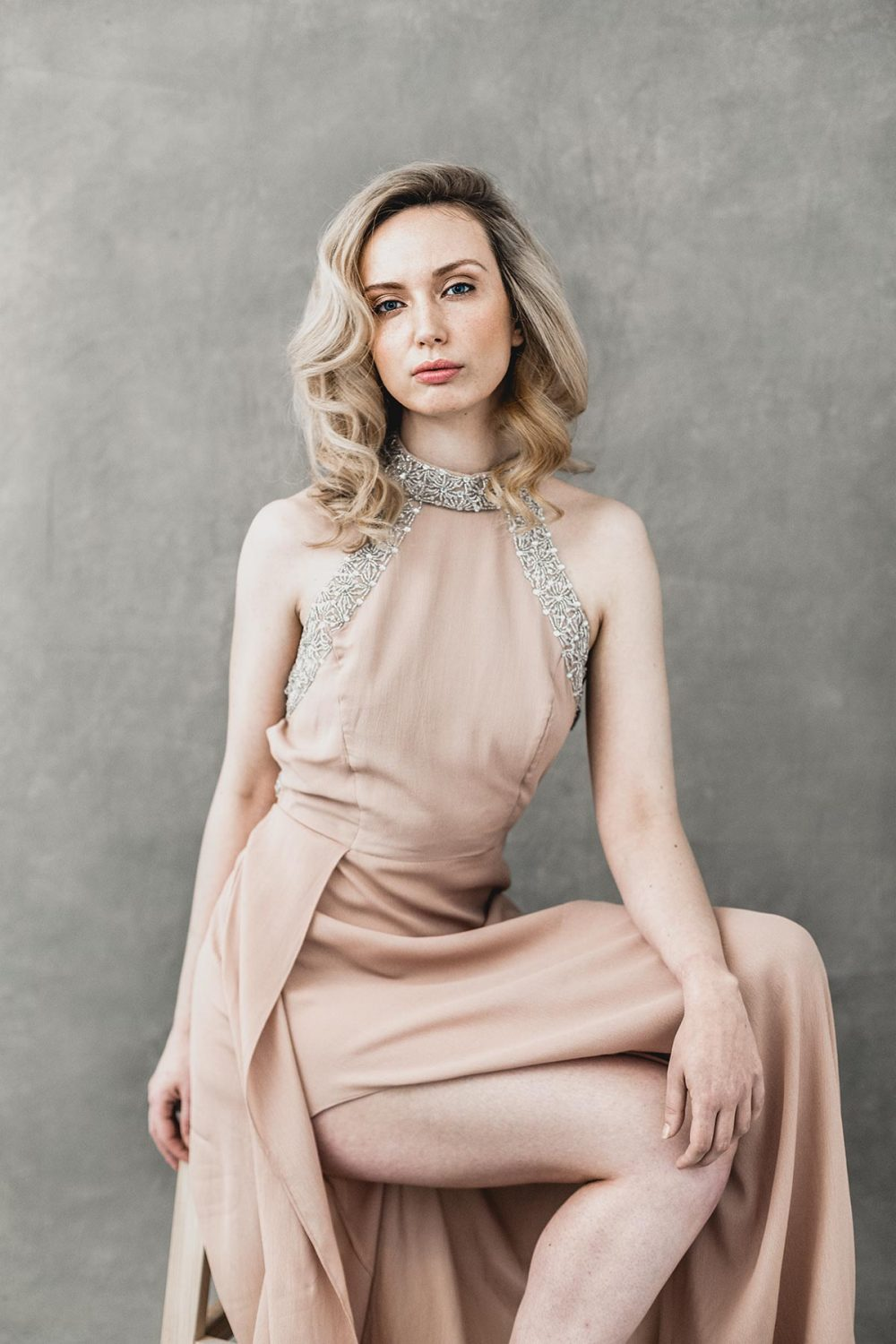 glamorous woman in a blush dress sitting on a stool