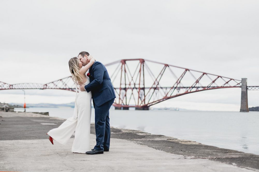 Newly wed couple stealing a kiss in front of the forth rail bridge in South Queensferry