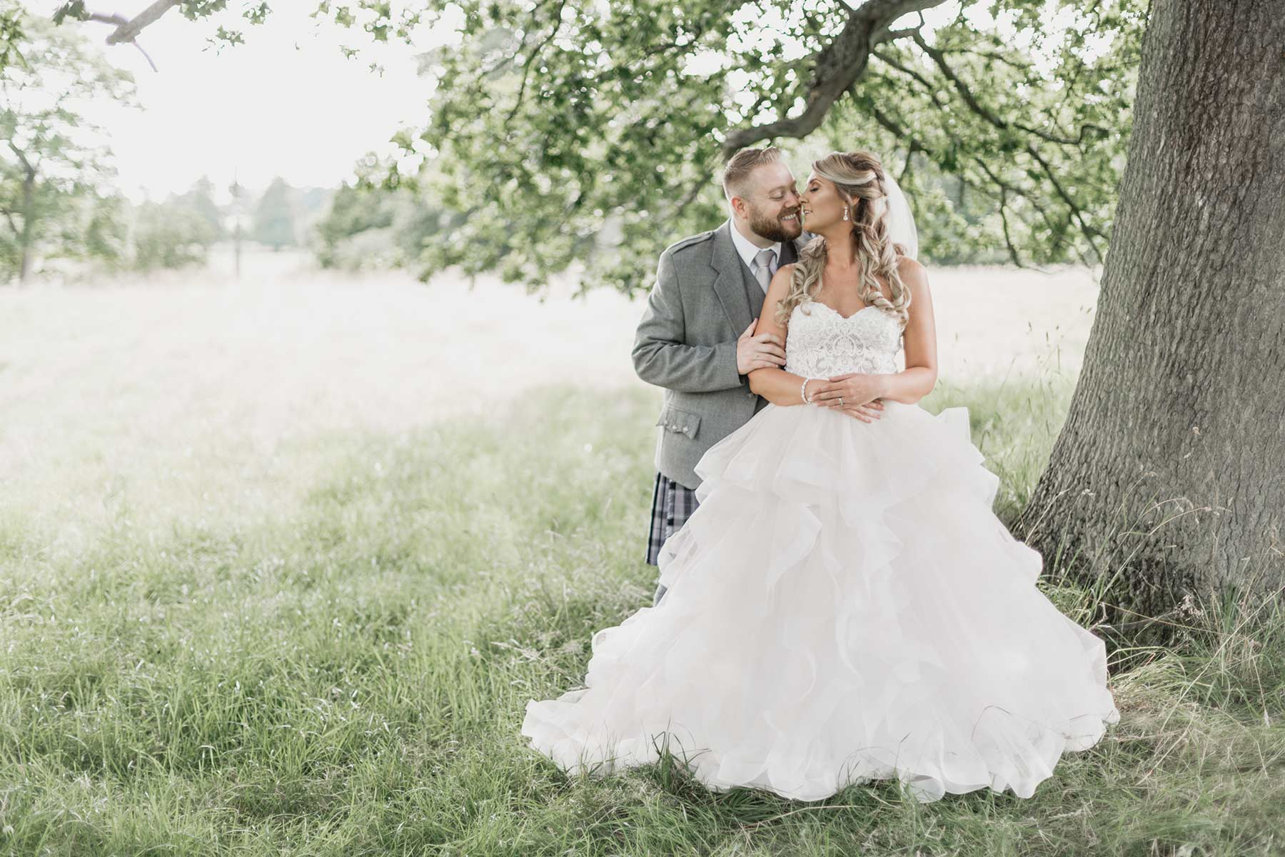 Romantic Wedding couple stealing a kiss under a tree