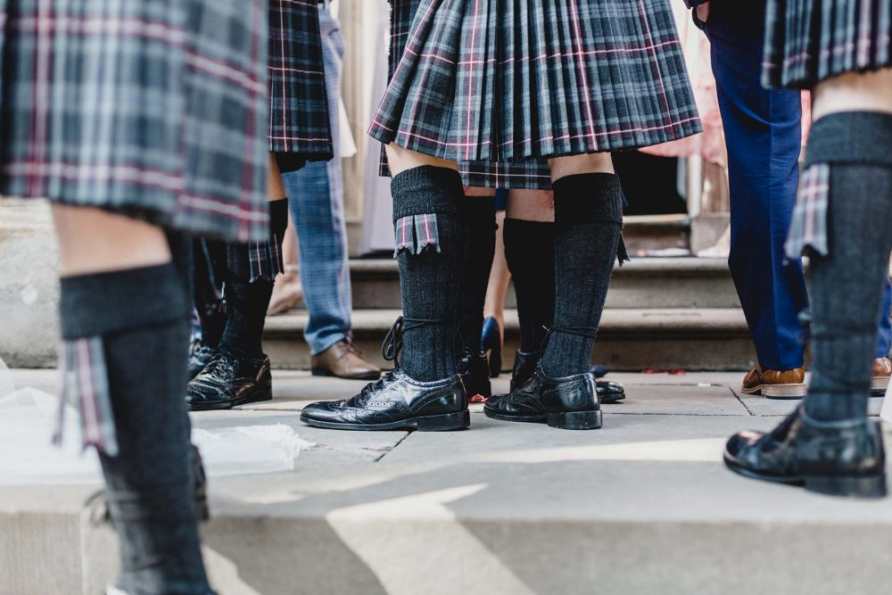 details of kilted guests at a wedding
