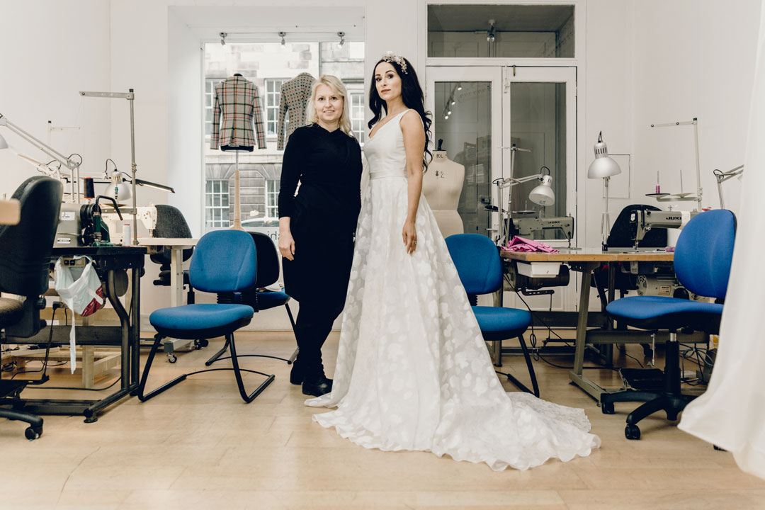 Mette from Freja Dress Designer with a bride in her studio