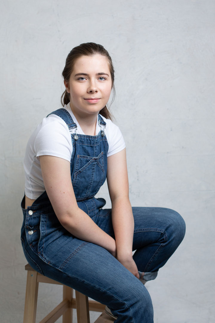 young girl in denim in front of a white backdrop
